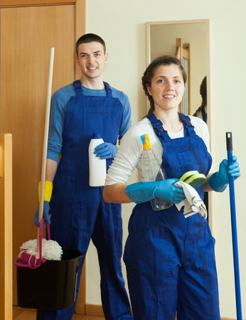 company premises: Handsome cleaners cleaning room at home Stock Photo