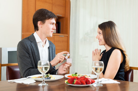 man gives jewelry pretty girlfriend during dinner photo
