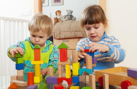 Deux enfants tranquilles jouer avec des jouets en bois � l'int�rieur de la maison Banque d'images - 27802267
