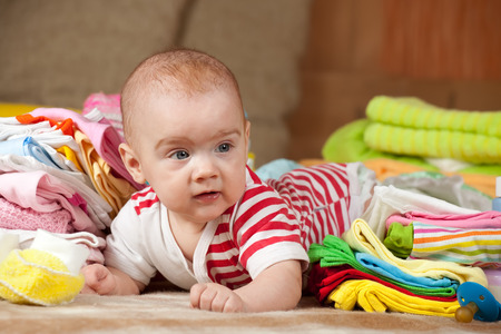 children's wear: baby girl with heap of childrens wear