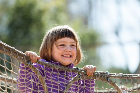 adroitness:  laughing girl climbing on ropes at playground  Stock Photo