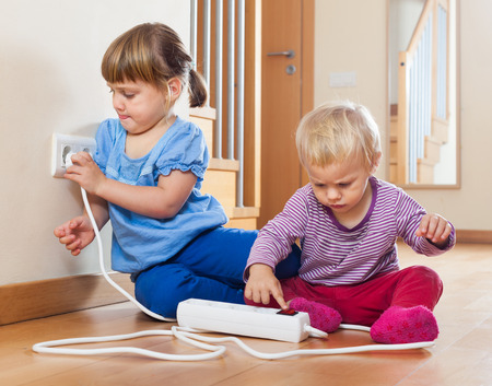 Two children  playing with electrical extension and outlet on floor at home photo