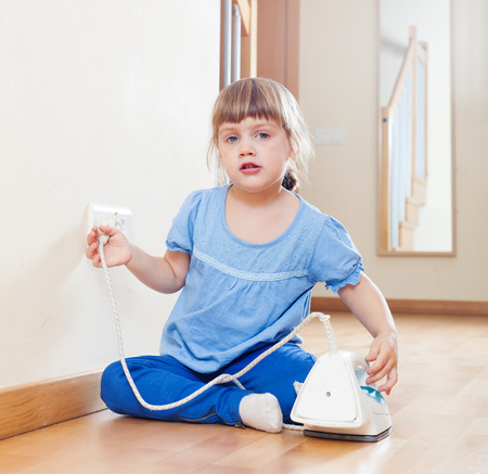three year old child playing with electric iron photo
