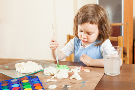Girl paints dough figurines in the room photo