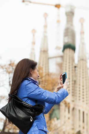 Woman with smartphone photographing herself against Sagrada Familia at Barcelona photo