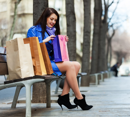 Smiling woman with shopping bags at street photo
