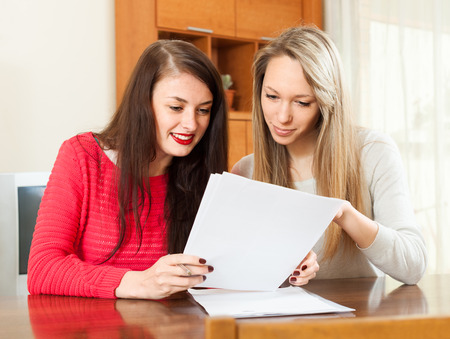 Two women works with financial documents in office photo