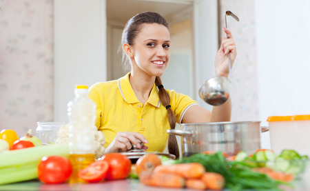 woman in yellow cooking with ladle in  kitchen  at home Stock Photo - 27822293