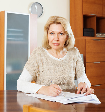 serious mature woman with financial documents