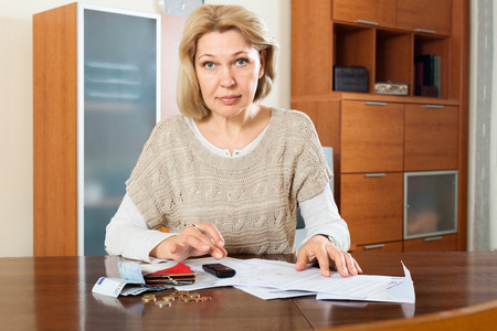 mature woman calculating money at  home Stock Photo