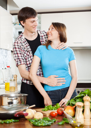 Young man flirting with girl in home kitchen photo