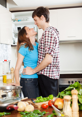 loving couple having flirt at home kitchen photo