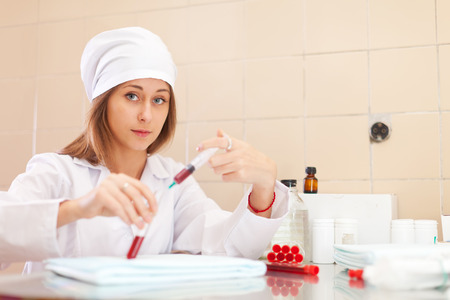 Young nurse works with blood sample in medical laboratory photo