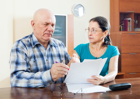 serious mature couple fills in questionnaire  at home photo