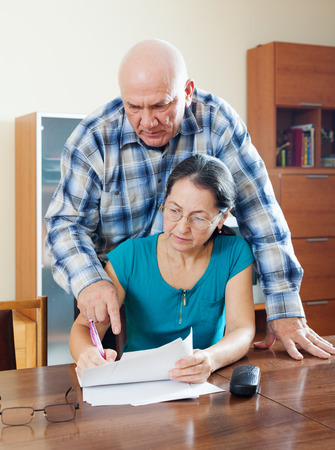 serious senior man with mature wife fills in questionnaire together at home interior photo