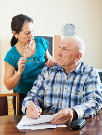wistful: wistful senior man with pensive mature woman fills in questionnaire together Stock Photo