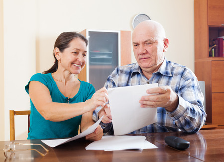 Happy senior couple holding financial documents at home   photo