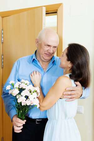 Senior man giving bunch of flowers to mature woman at home photo