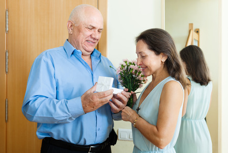 Senior man came to mature woman with present  at home  photo
