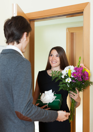came: Pretty girl giving flowers and gift to guy at home door
