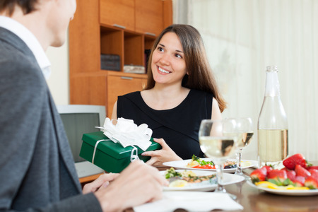 encounter: Girl giving gift  to man at table during romantic dinner in home