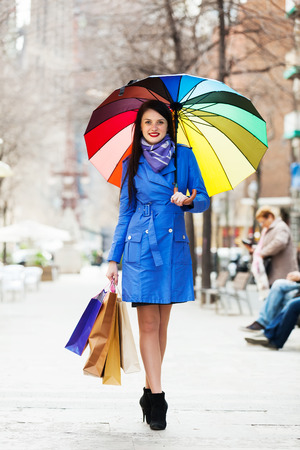 full length shot of happy woman with shopping bags and umbrella photo