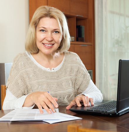 Smiling mature woman with laptop and financial documents at home interior Stock Photo