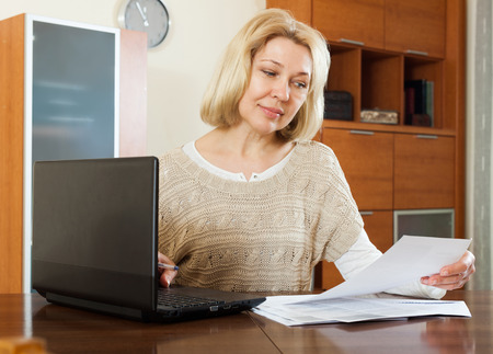 Mature blonde woman staring financial documents with laptop  at table in office interior photo