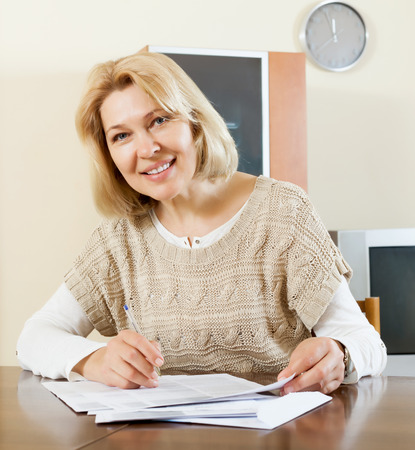 home office interior: Smiling mature woman filling in paper at home or office interior