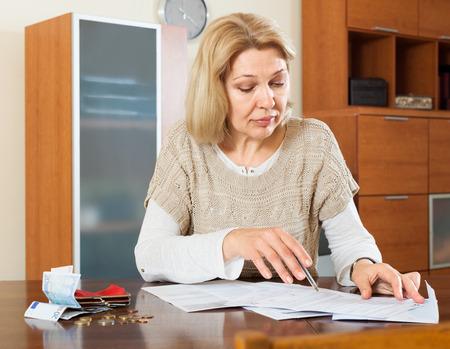 decide: Mujer de Eldery calcular el presupuesto de la familia en el hogar Foto de archivo