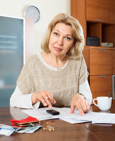 parsimony: Eldery woman calculating the family budget at  home Stock Photo