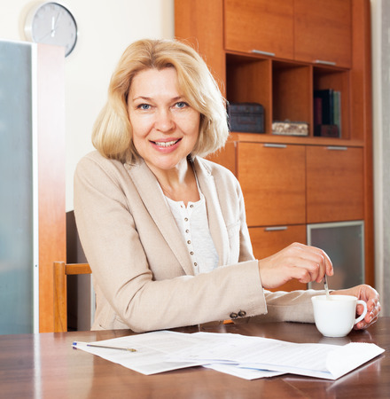 parsimony:  smiling mature woman working with  documents at table in home