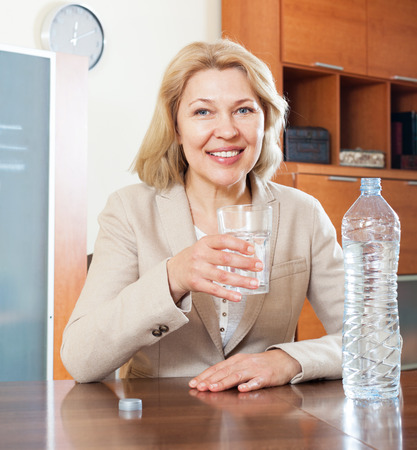 mature businesswoman at desk with glass of water photo