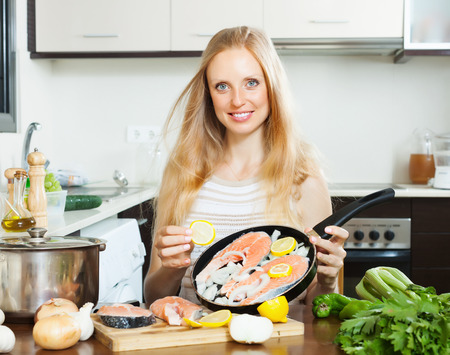 cheeful:  woman putting pieces lemon in fish at  kitchen Stock Photo