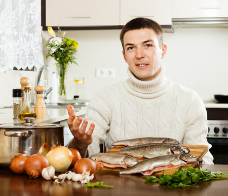 Handsome man with raw trout fish at  kitchen  photo