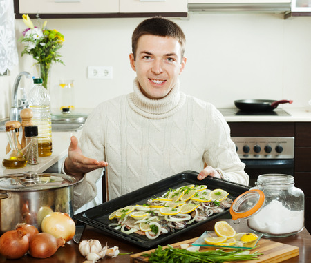 Smiling guy cooking trout fish with lemon in roasting pan photo