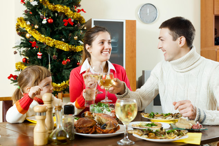 Portrait of Happy family of three celebrating Christmas  over holiday table at home interior photo