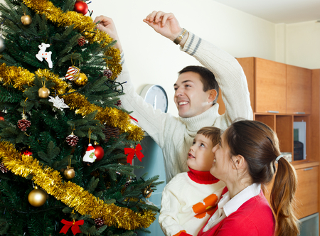 Parents and baby girl decorating Christmas tree at  home with  Christmas tree photo