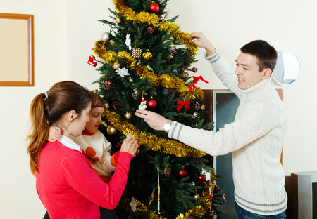 Happy parents and child decorating Christmas tree at living room photo