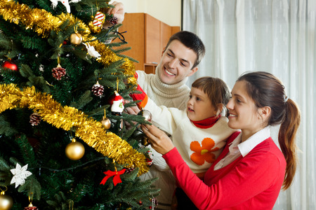 young parents   and child preparing for Christmas at home photo