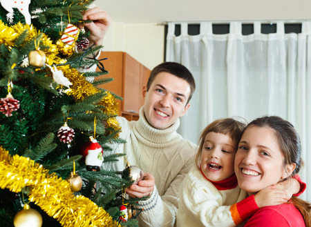 Happy family of three preparing for new year at home photo