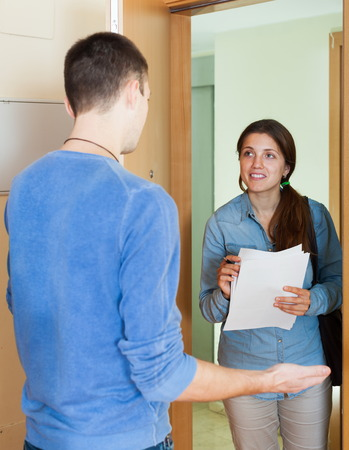 Smiling employee talking with man with paper in door photo