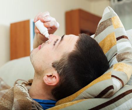 nasal drops: Man dripping nasal drops in living room Stock Photo
