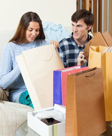 Woman showing purchases  to  boyfriend at  home  Stock Photo