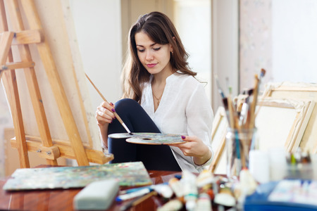 워크숍에서 캔버스에 긴 머리 아름다운 예술가 페인트 스톡 콘텐츠