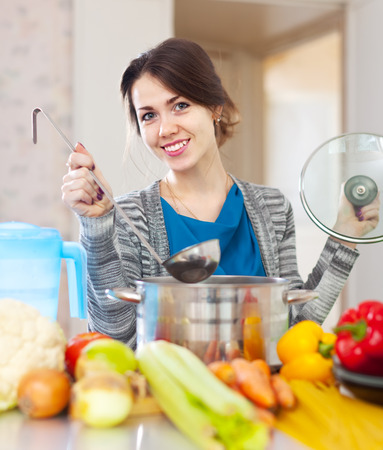 Happy  woman cooking veggie soup with laddle in  kitchen  at home photo