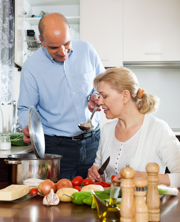 Senior with mature wife smiling and preparing food together in domestic kitchen photo