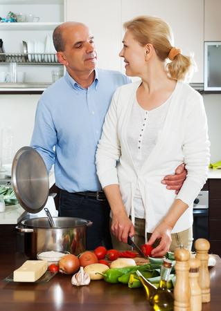 spaniard: Elderly couple cooking Spaniard tomatoes at home kitchen