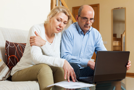 Family reading finance documents together and using laptop in home interior photo