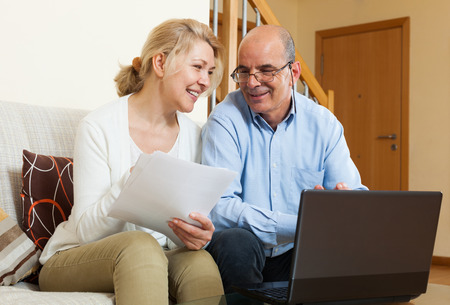 Happy mature couple with financial documents and notebook in home interior photo